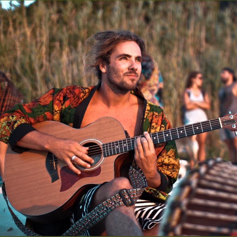 Sean Koch trägt bcos ordinary sucks batik kimono spielt gitarre am strand in südafrika
